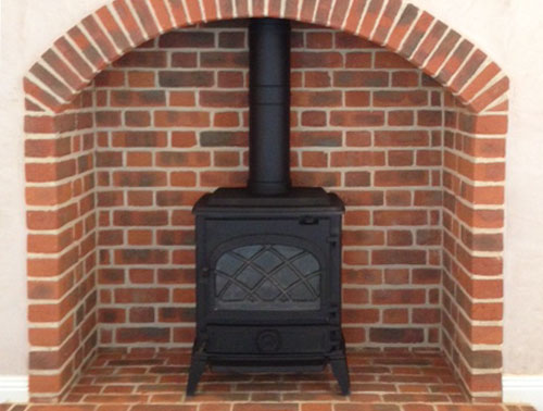wood stove installed in brick fireplace & hearth